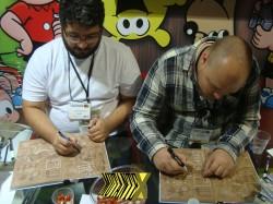 Eduardo Damasceno e Luis Felipe Garrocho autografam na Bienal de SP (e o Bugu querendo aparecer, como sempre!) - Foto: Júnior Batson